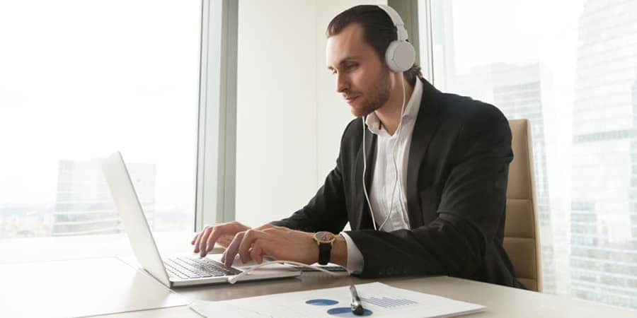 Man works on his computer while wearing headphones.
