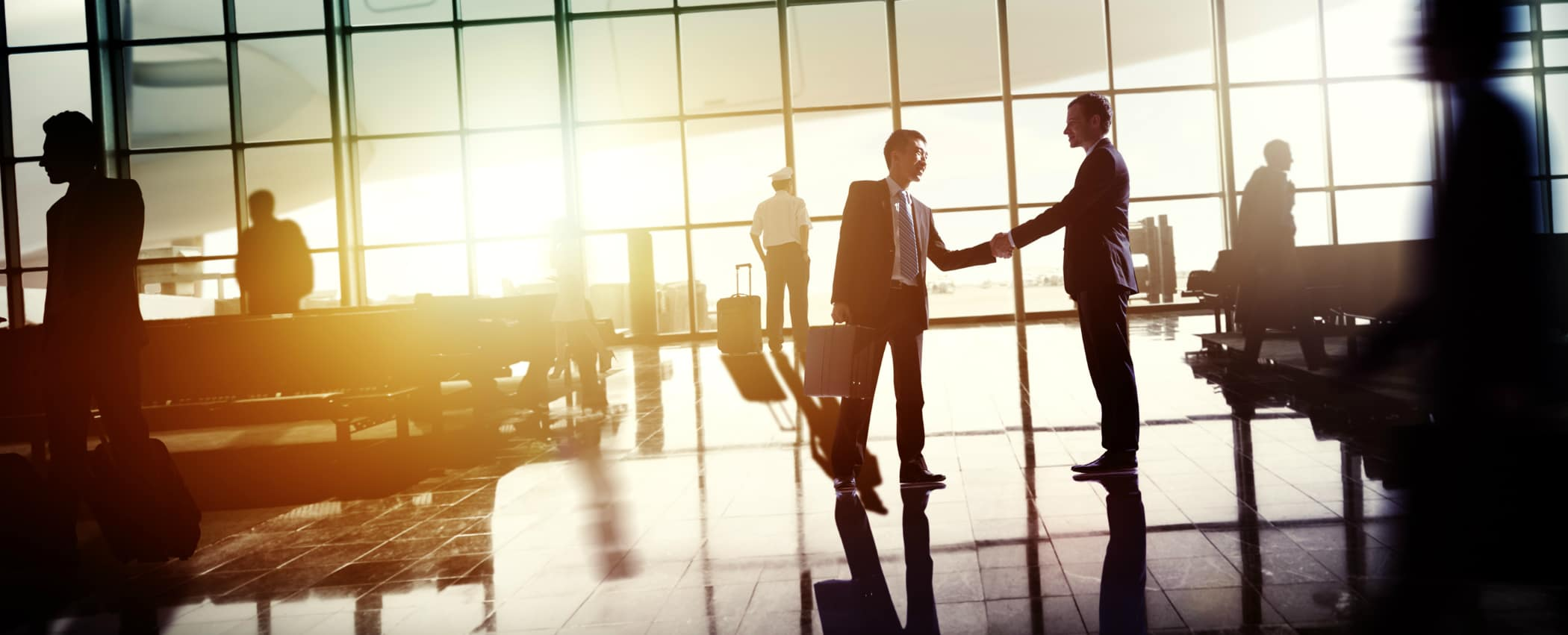 Two executive men shake hands by a private plane.